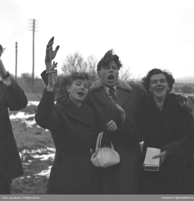 Tre glade, syngende personer. To kvinner og en mann. Det står også en mann i venstre billedkant. Sannsynligvis venner av Fridtjof Jacobsen
