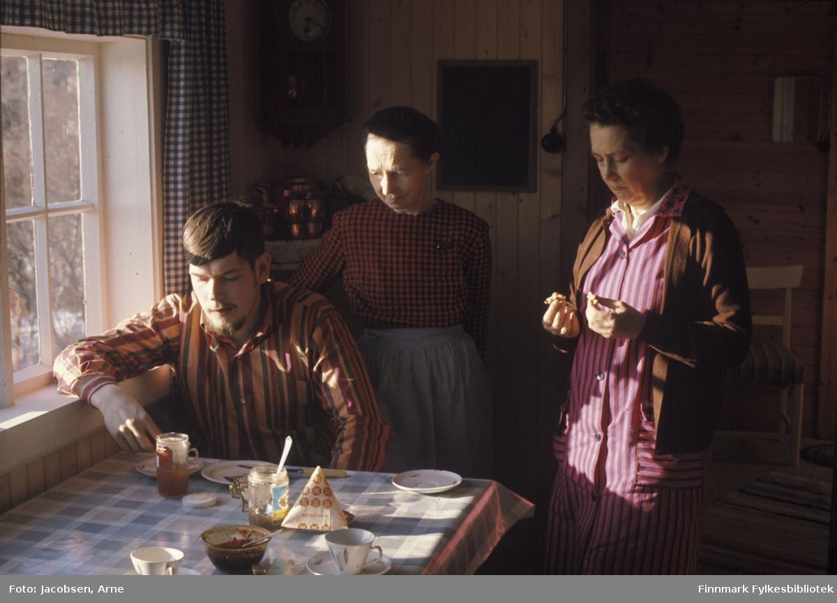 Frokost på hytta. Sigurd Logn med stipete skjorte sitter ved bordet. Rett bak han står bestemor Sigrid Nakken med rutete overdel og forkle på seg. Til høyre står Aase Jacobsen med stripete skjørt med lik overdel og en mørk jakke på seg. Bordet har rutete voksduk og flere tefat og kopper står oppå. Syltetøyglass med skje oppi og en skål med syltetøy også den med skje oppi står framme. En pakke fløte står på et tefat. Sigurd sitter med armen i vinduskarmen på sprossevinduet. Rutete gardiner henger på vinduet, en klokke henger i hjørnet over et skap med en kjel og pynteting på. Et speil på veggen ved siden av en lysbryter. Stående panel på veggen. I rommet bak med liggende panel henger et speil, en trestol med stripete pute står på gulvet og en matte går på skå over gulvet.