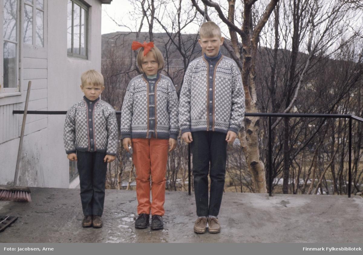 Tre barn, to gutter og en jente, står pent oppstilt i like strikkekofter. De er, fra venstre: Øystein, Astri og Sigmund Nakken. Astri har knytt en sløyfe i håret. Guttene har mørke bukser og hun har en lysere olabukse på. Terrassen de står på har betongdekke med et enkelt, sort lakkert metallrekkverk. Trærne i bakgrunnen har ikke løv og noen snøflekker kan ses på bakken så bildet er nok tatt sent på våren. En kost står lent mot rekkverket og det er noen vannpytter på terrassen.