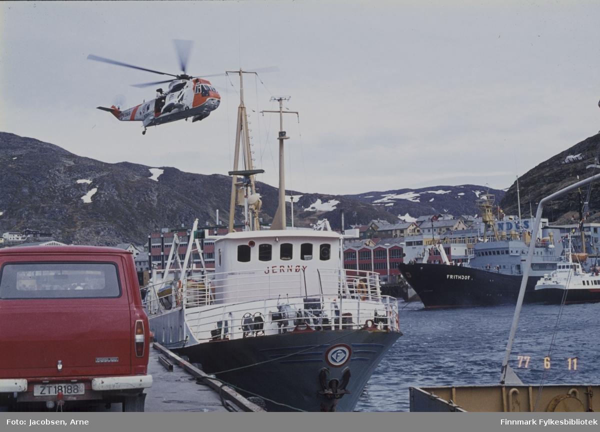 """Et Sea-King redningshelikopter demonstrerer redning i Hammerfest indre havn. FFR-båten Jernøy ligger ved kai og over havna ligger Troms Fylkes Dampskibsselskap (TFDS) sin """"Fjordkongen"""", utleid til FFR . (Det er to vesentlige ting som viser at dette ikke er et FFR fartøy, FFR hadde grå skrogfarge, mens båten på bildet er svart. Nummer to er den røde stripa som vises fra det tredje salongvinduet fra venstre. TFDS hadde røde striper på sine hurtigbåter. Rorhuset på """"Brynilen"""" sto også noe lengre bak enn det gjorde på de fleste andre Westamaraner, grunnet lasterommet som var i forkant av brua.) Ved siden av den ligger et stort skip, Frithjof. Over baugen til den ser vi deler av Findus-anlegget og fjellet Salen bak. Til venstre i bildet står en Ford Transit varebil parkert på kaia og Mollajellet ses i bakgrunnen. Nede til høyre ses hekken på en annen båt, muligens FFR-båten Sørøy."""