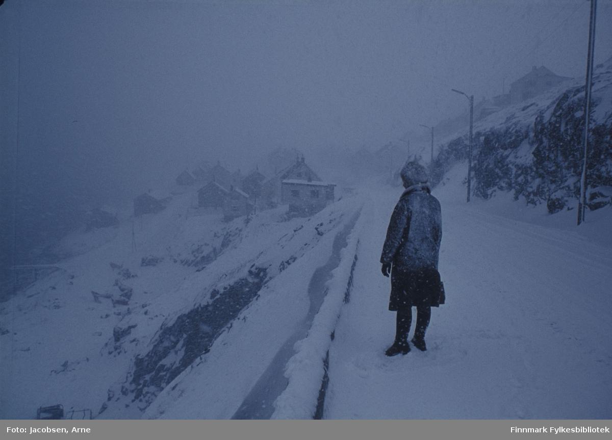 Aase Jacobsen på tur til byen i snøkov. Hun står i nedre del av Klinkastupet(Rv 94) inn mot Hammerfest. Hun har mørke vinterklær på og en veske i den hanskekledte handa. Ryggen på jakka og baksiden av lua er snødekt. Det er ikke så mye snø i terrenget, men det er dårlig sikt pga. snøbyger så vi ser stort sett bare de nærmeste husene i Akkarfjordveien. Man kan såvidt skimte et par hus i Gammelveien oppe til høyre. Lyktestolpene står på rekke og rad på høyre side og på venstre side ser en kantsteinene.
