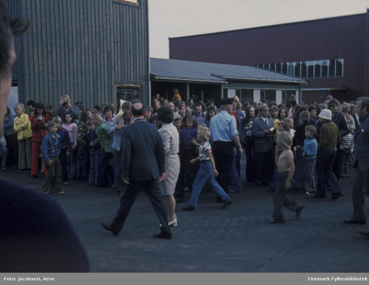 Åpning av Hammerfest lufthavn. Midt i bildet går daværende ordfører Arnulf Olsen og samferdselsminister Annemarie Lorentzen. Begge er pent kledt, han i mørk dress og lakksko, hun i skjørt og hvite sko. En uniformert politimann står, med ryggen til fotografen, og holder orden på folkemengden som har møtt opp, bl.a mange barn. Bygningen til venstre er tårnet, i midten står passasjerterminalen og til høyre hangaren.