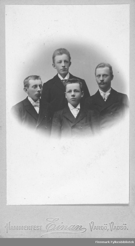 Gruppeportrett av fire unge menn. Gutten til venstre er Jacob Sigvart Jacobsen. Han var sønn til smedmester i Vardø. Ole Sigfrid og hustru Anna Christine Vibe Jacobsen. Jacob Sigvart overtok farens smedverksted. De andre tre personene på bildet er ukjente
