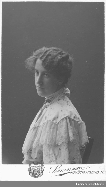 Portrett av ukjent kvinne. Kvinnen sitter på en stol. Hun er kledt i en lys blomstret kjole eller bluse med blonder. I halsen har hun festet et smykke