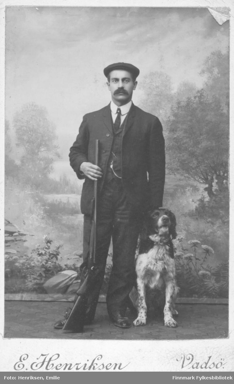 Portrett av en ukjent mann med bart og en hund. Bildet er tatt i et fotoatelier. Mannen er kledt i en mørk dress og vest. Han har hvit skjorte og et mørkt slips. På hodet har han en lue. I hans høyre hånd holder han et gevær