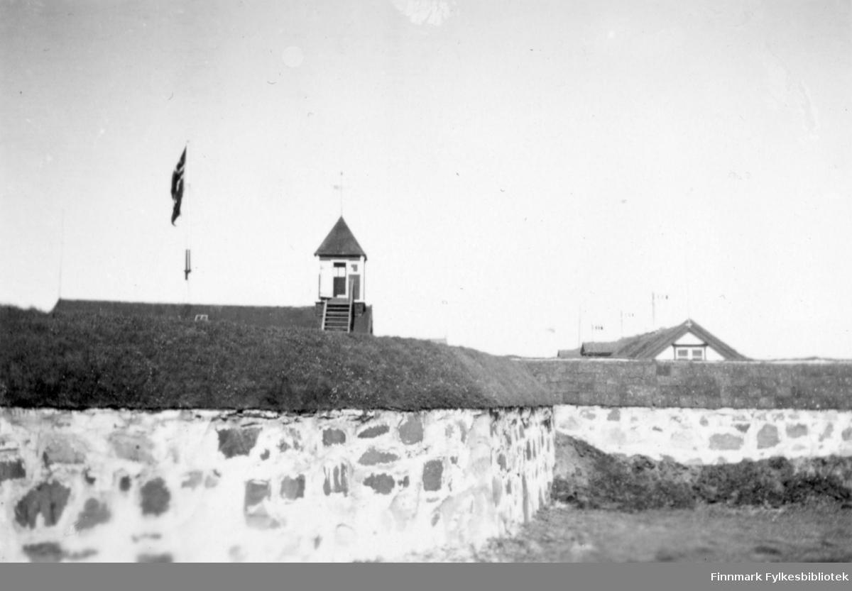Fotografi fra Vardøhus Festning. I forkanten av bildet ser man en murkant med en torvvoll øverst. På innsiden av muren kan man se øverste del av noen bygninger. Det går en trapp oppe på taket til et tårn på den ene. På bildet er det også en flaggstang med det norske flagget heist