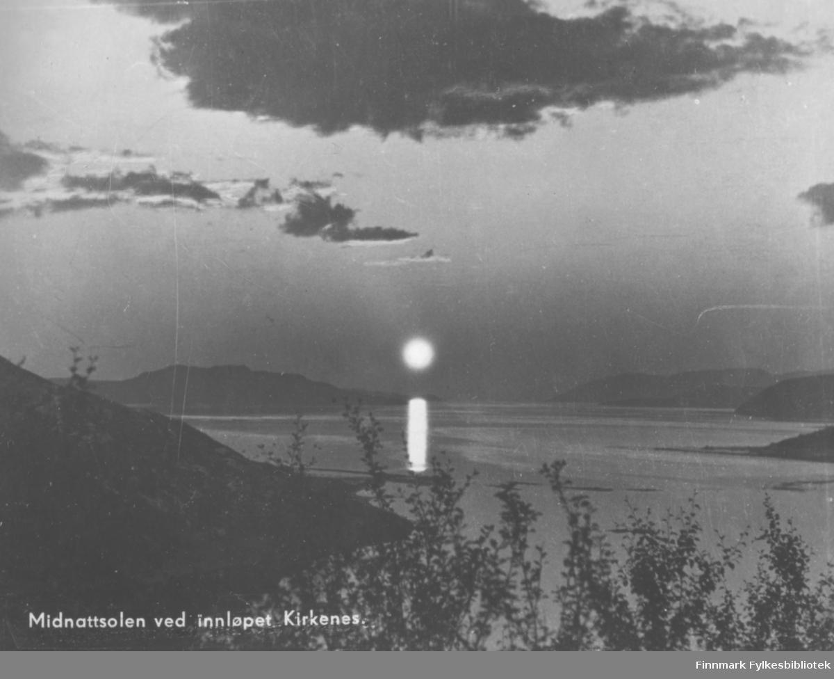 Postkort Fra Kirkenes. Midnattsola speiler seg i sjøen ved innløpet til Kirkenes. Vannet er omkranset med fjell. Det er noen mørke skyer på himmelen. I front av bildet kan man se trær