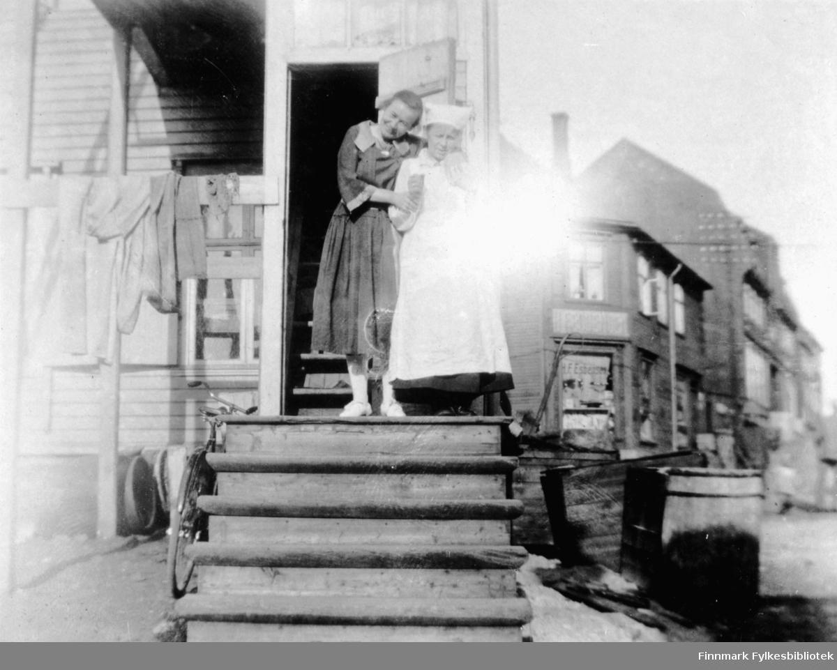 Fotografi fra Vadsø siden H. F. Esbensen, står det på butikken bakgrunnen. Oppe på en trapp foran en åpen dør til et hus står det to kvinner. Kvinnen til venstre er kledt i en kjole og hun holder om skulderen på den andre. Den andre damen er kledt i et hvitt forkle og har et hvitt skaut på hodet. Bildet er tatt i en gate. Til høyre ser man flere bygninger. Til venstre for trappen står det en sykkel og til høyre står det noen trekasser på bakken.