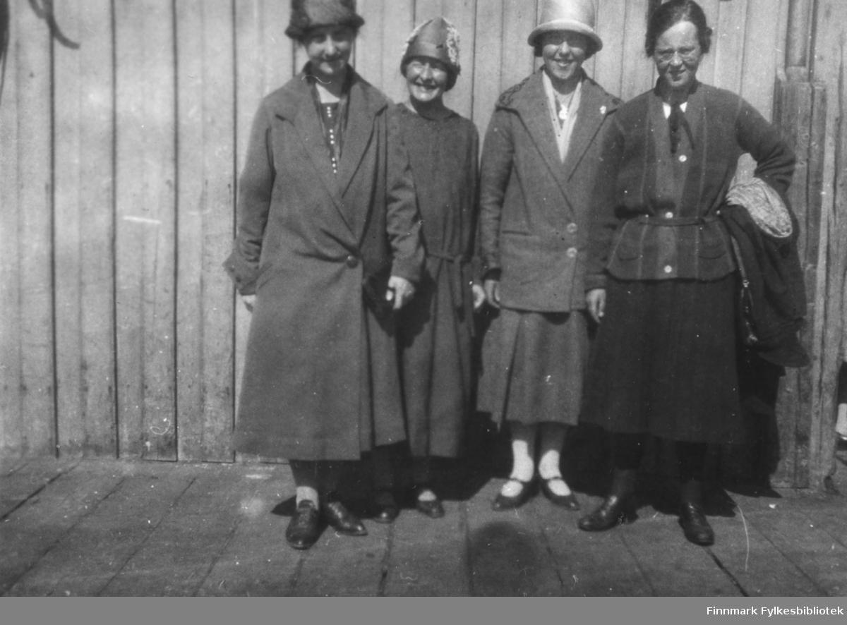 Fotografi av fire kvinner. Lærerinne Julie Jacobsen fra Vardø står som nummer to fra venstre. Hun var datter til smedmester i Vardø Ole Sigfrid Jacobsen og hustru Anna Christine Vibe Jacobsen. De andre kvinnene er ukjente. Kvinnen til venstre er kledt i en mørk kåpe, Julie har på seg en mørk kjole. De to andre kvinnene har på seg mørke jakker og skjørt. Kvinnen til venstre har klær hengende over armen sin. Tre av damene har hatt på hodet. De står på et tregulv foran en trevegg