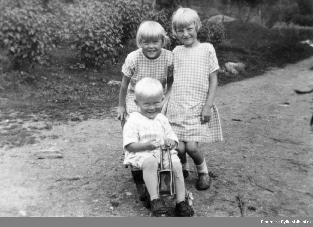 Fotografi av søskene Liv, Gerd og Finn Vibe Jacobsen fra Bergen. De er barn av August Magnus Jacobsen fra Vardø og hustru Solveig Johannessen Jacobsen fra Bergen. På bildet sitter Finn i en trillebår. Han er kledt i en lys  rutet skjorte og kortbukse. Ved den venstre foten hans er det en liten lekehest som han har tau i. Liv som står bak han og Gerd er kledt i likedanne smårutete kjoler. Bildet av barna er tatt ute på en grusveg. Det er trær i bakgrunnen