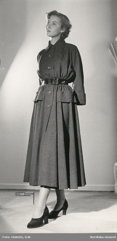 """Nordiska Kompaniet. Kvinna i mörk klänning med rynkad kjol. Markerad midja med brett skärp. Text på baksidan: """"Hardy Amies Höst -48"""""""