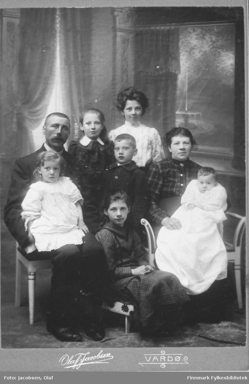 En familie på 8 fotografert i ateliere studio hos Olaf Jakobsen i Vardø. Familien kan ha vært bosatt i Ekkerøy (albumet kommer derfra).  Bildet er tatt i anledning minstebarnets dåp. Spedbarnet som sitter på morens fang er kledd i dåpskjole. Ellers har familien fire jenter og en gutt.  Faren sitter til venstre med en jentunge på fanget. Kvinne mann gutter jenter. Malt bakgrunn