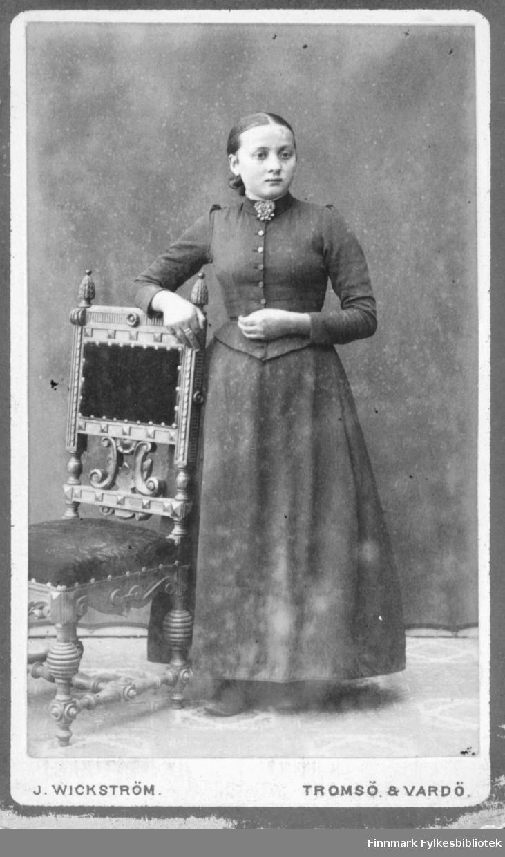 Portrett av ei ung jente, kanskje konfirmasjonsbilde, hun står med en hånd over ryggen på en stol iført kjole og brosje i halsen. Hun har en stor ring på høyre langfinger. Albumet med bildet kommer fra Ekkerøy, kanskje hun bodde der.