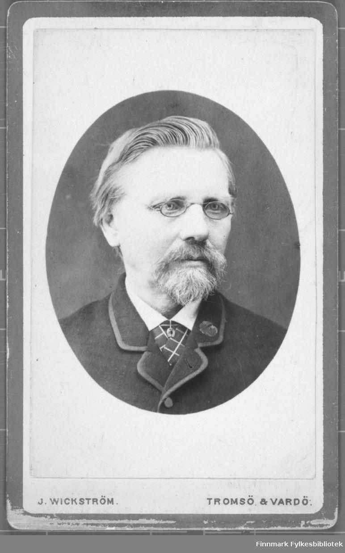 Brystportrett av mann med briller skjegg og bart. Sikkert en lærer eller utdannet person. Studio ateliere Albumet med bildet kommer fra Ekkerøy, kanskje han bodde der.