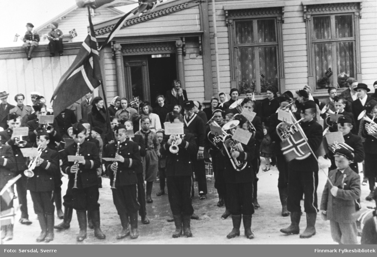 17. mai i Vardø 1952. Bildet av korpset som spiller. Barna i korpset har unifom på. De står og spiller foran et hus.