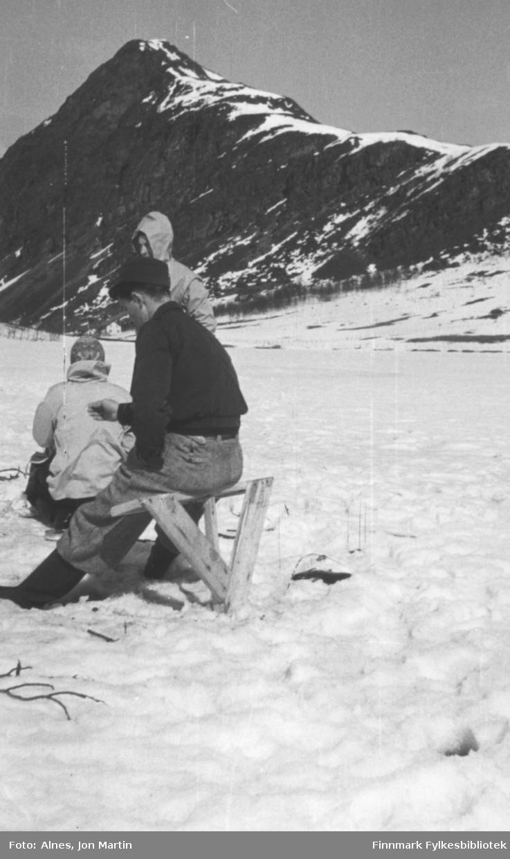 Magnus Wilhelmsen sr. (litt usikkert om det er ham) på isfiske på Vassdalsvannet i Øksfjord, våren 1955