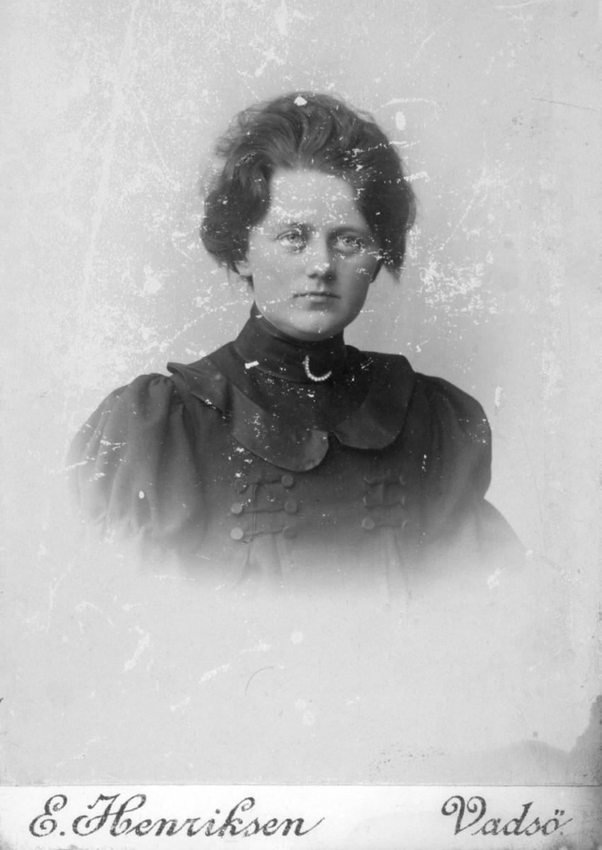 Et portrett av Olga Pedersen. Hun er kledd i kjole med et dekorativt bærestykke, den er dekorert med flere knapper og bånd. På halsstykket har hun en vakker brosje. Fotografiet tatt på begynnelsen av 1900-tallet.