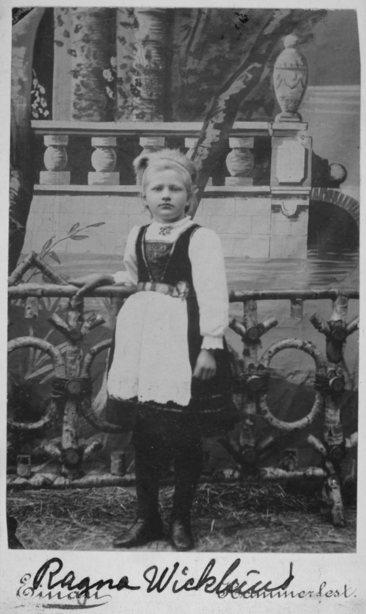 Portrett av ei jente, kanskje 5-6 år gammel - Ragna Wicklund. Hun var datter av Christian Jacobi Wicklund og hustru Anna Margrethe, f. Ulich. Ragna giftet seg med fisker Eilert Isaksen (som seinere tok etternavnet Nilsen) i Kjøllefjord, og sammen hadde de 11 barn