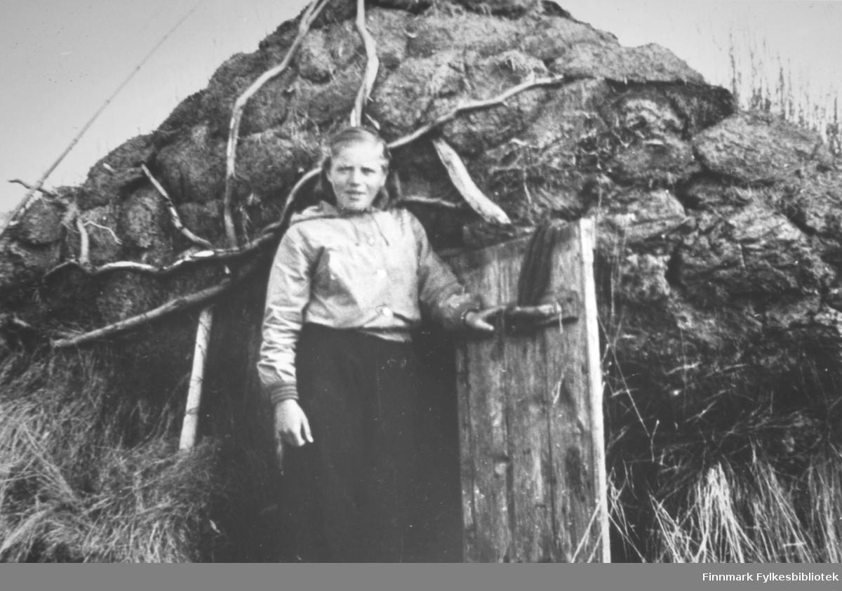 Ung jente, Solveig Harila (g.Nilsen), fotografert ved en gamme ved Østervannet. Hun står ved døråpningen og ser rett på fotografen. En fiskestang står lent mot gammen ved siden av henne