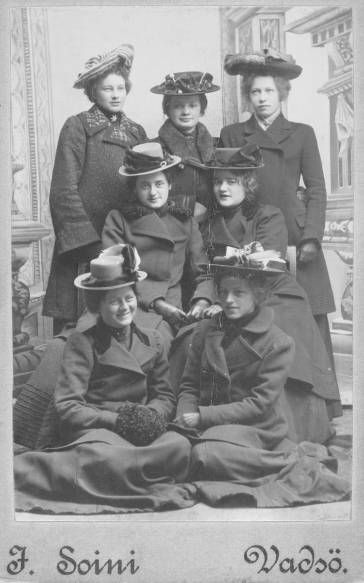 """Gruppebilde av syv unge kvinner. To av dem, sitter på gulvet; Olga (Marie) Pedersen (til venstre) og Johanne Møller (til høyre), sittende på stoler; Karen Balke og Astri Froskeland. Stående bak fra venstre; Magnhild Simonsen, Andrea Samdahl og Sigrid Grønvigh. Alle er kledd i yttertøy, med kåper, kunstferdige hatter med fjær og hansker på hendene. Fotografiet er tatt i fotostudio med en tidstypisk malt bakgrunn med antikke søyler. Bak på visittkortfotografiet har fotograf Emilie Henriksen, Vadsø, skrevet navn og alder på pikene:  Magnhild Simonsen 18 år Andrea Froskeland 19 år Sigrid Grønvigh  17 år Karen Balke 16 år Astri Froskeland 15 år Olga Pedersen 17 år - registrert i Digitalarkivet som Olga Marie Pedersen født 1885, død 1912. Kontordame/kontorist på Amtskontoret i 1910. Johanne Möller 15 år  Vadsø den 28.april 1903 """"Banden"""" """"Knoppene"""" står det også - antagelig en karakteristikk av venninneflokken."""