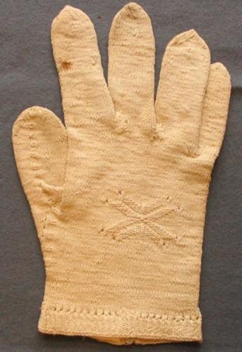 Högerhandens fingervante, stickad i tunnt oblekt bomullsgarn. Liten resårkant 12 mm, hopstickade maskor som bildar en hålrad efter resåren. Kant från lillfingerns insida ner till resåren med partier om aviga och räta maskor, likaså runt tummen och upp på tummen från två håll. På ryggsidan finns en stjärnform i aviga/räta maskor, 45 X 30 mm.