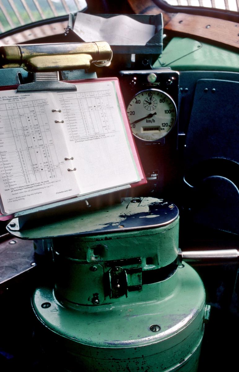 Kjørekontroller på NSB dieselelektrisk lokomotiv Di 3 603 (NOHAB/GM 1957). De første lokomotivene (602 - 607) hadde denne runde konsollen i metall, som er orginalt GM Electro Motive Division -utstyr Plassen for motstandsbrems er blendet, ettersom Di 3 ikke ble utstyrt for dette. Over konsollen ser man Rutebok for Trondheim distrikt 1982, med rute for godstoget 5772 Namsskogan - Trondheim. I bakgrunnen hastighetsmåler type Hassler.