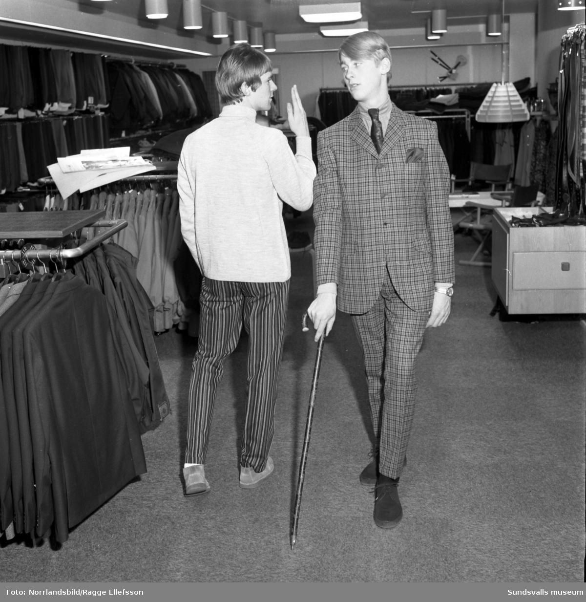 Manliga mannekänger visar kläder inne på Henrix herrekipering för annonsfotografering.