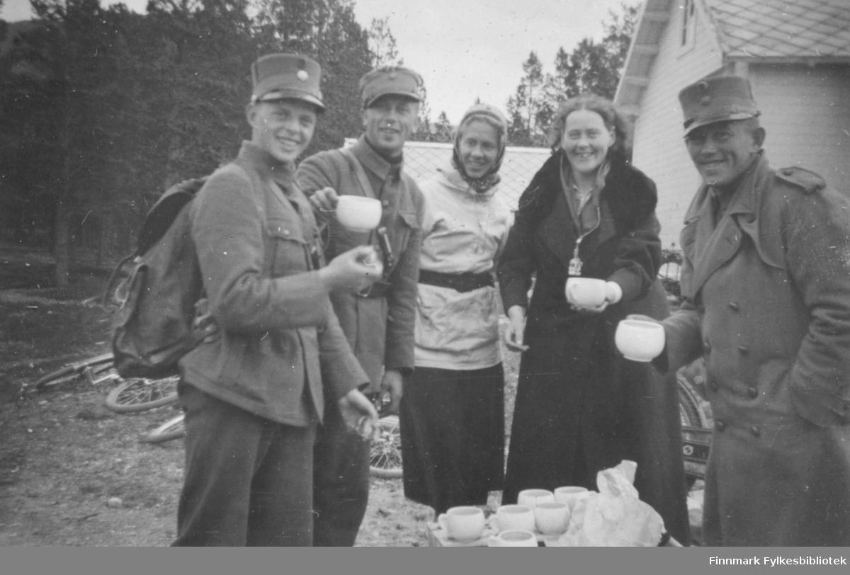 Soldater og sykepleiere drikker kaffe utendørs. I bakgrunnen ligger sykler slengt på bakken. Bildet kan være tatt på en matstasjon under utmarsj