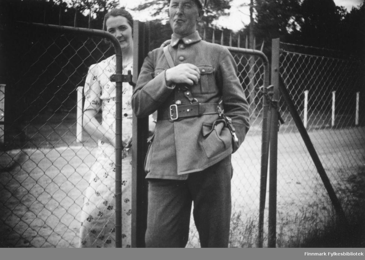 En soldat og kona hans atskilt av et gjerde. Innskrift i album: Haldorsen og frue. Innenfor gjerdet i kongens klær
