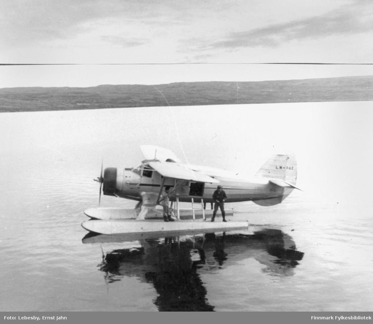 """Fotoserie fra tur med sjøfly til Peskvannet 12. og 13.august 1955. Per Bjørgan forteller: """"Vi hadde ikke båt med til Peskvannet, men dorget med flyet i stedet. På flottøren står Karl Jakob Carstens og Ole Gustav Øverdahl. Ut av cockpitvinduet stakk en lengere fluestang. Motoren ble stilt så lavt som mulig, slik at propellen såvidt slo rundt. Fisken brydde seg ikke om hverken flyet eller motorduren, men beit villig vekk."""" Foto: Ernst Lebesby."""