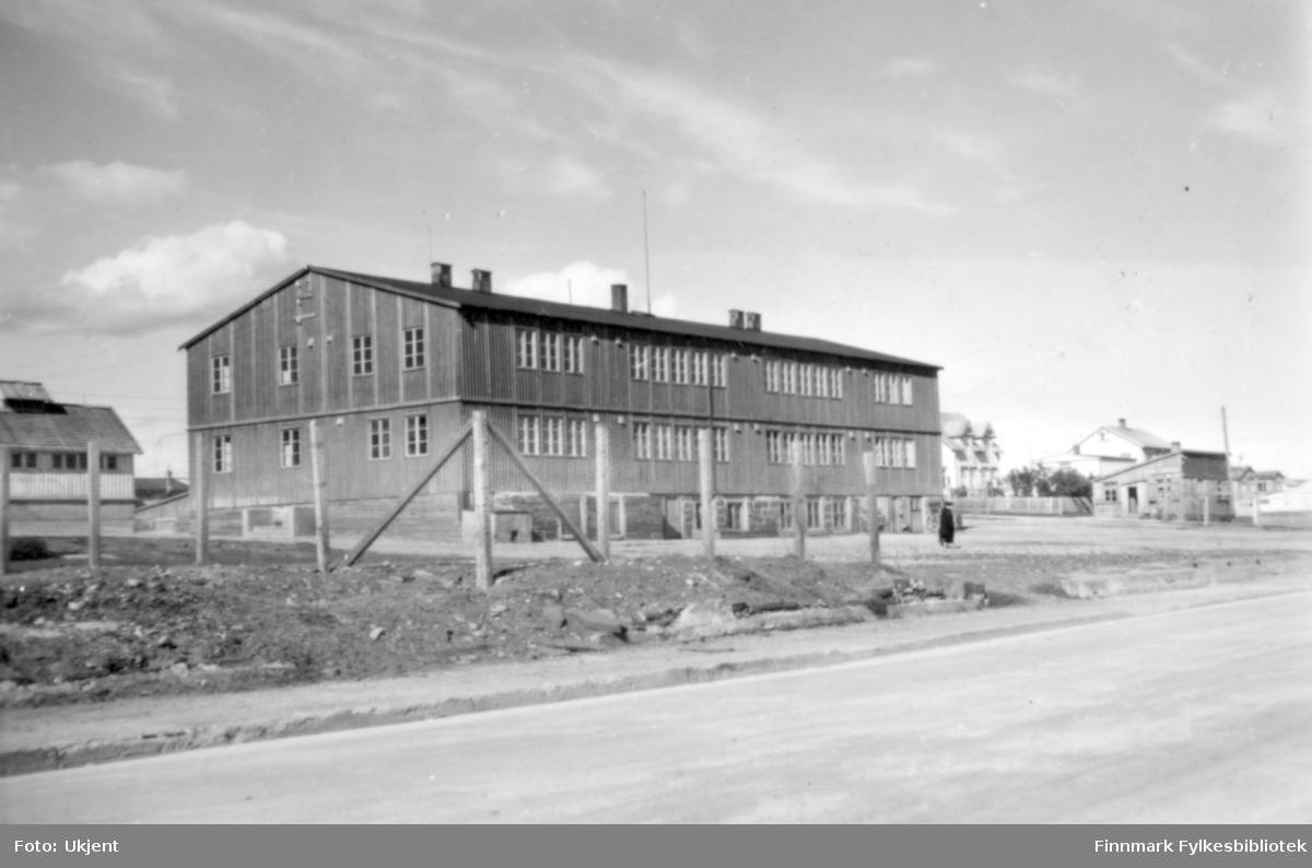 Skolebrakka, som ble satt opp i 1946 på grunnmuren til den gamle Folkeskolen, og som hadde klasserom for både folkeskolen og realskolen i Vadsø. Til høyre brakka der Johan Grønvigh hadde sine forretning. Foto: ukjent.