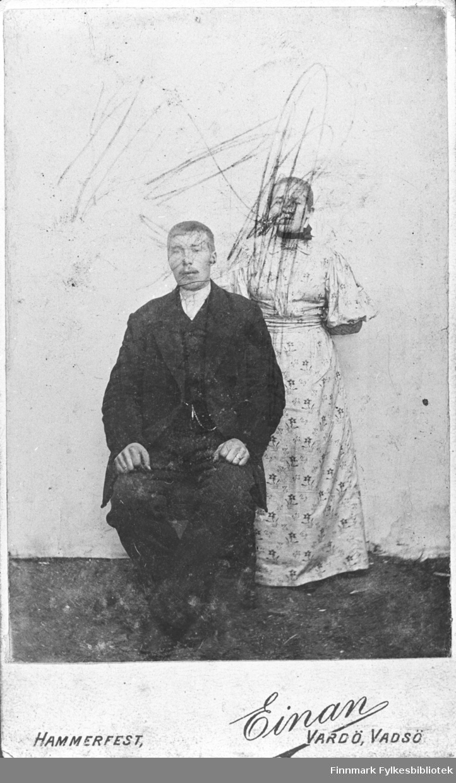 Et ung par fotografert hos Einan I Vadsø. Paret er ikke identifisert, men hører til Palo/Wara slekten. På bildet: mannen sitter og kvinnen står bak han kledd i en lys kjole. Noen har tengnet (barnetegning) på personene.