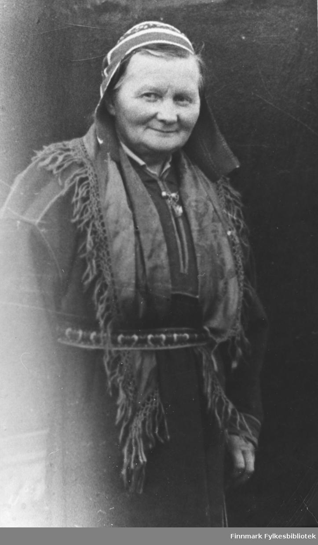 En eldre samekvinne står ved en mørk bakrunn (vegg?) kledd i kofta og lua. hun ser mot fotografen og smiler vennlig. Kvinnen er ukjent.