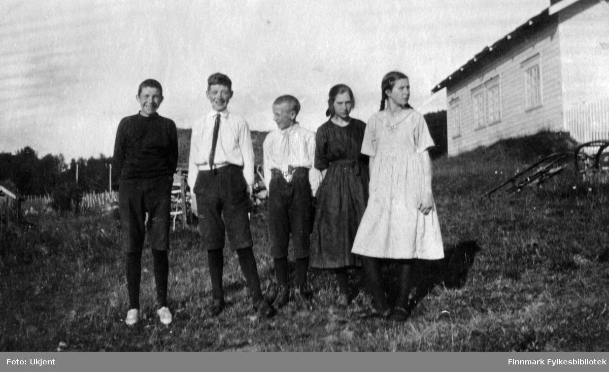 Dette bildet er tatt nedenfor huset på gården Strømsnes i Jarfjord. Fra venstre: Kaare Espolin Johnson, Einar Bertelsen, en ukjent gutt, Aagot Bertelsen (?) og Elsa Bertelsen (?). Jentene har på seg kjoler, sko og strømper. Piken helt til høyre har flettet hår. Einar og den ukjente gutten har på seg slips og skjorte. Kaare har på seg en genser. Alle guttene har knebukser, strømper og sko. I bakgrunnen kan man se et gjerde og huset til høyre har fire vindu. Ved siden av huset kan man se noe som minner om en slede som ligger opp ned.
