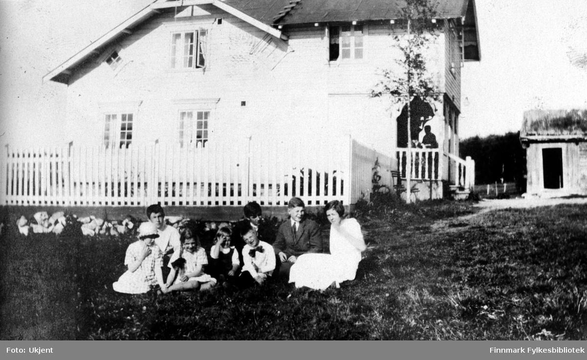 Bildet er tatt fra gården Strømsnes i Jarfjord sommeren 1924. En gruppe av barn sitter på plenen ved siden av huset. En del av barna er ukjente. Bakerste rad fra venstre: Kaare Espolin Johnson, Einar Bertelsen, ukjent gutt og Elsa Bertelsen. Barna i første rad er uidentifiserte, men har tidligere i originalalbmuet blitt betegnet som 'Tulla, Bisse, Busse og Bollebas'. Jentene har på seg sommerkjoler. Piken helt til venstre har på seg en hatt. Piken ved siden av har flettet hår med sløyfer. Gutten i første rad har en stor sløyfe rundt halsen. Guttene i bakerste rad har på seg slips og skjorte. Bak gruppen kan man se at det er blitt satt opp et gjerde. Inngangspartiet på huset er blitt laget med dekorative søyler og det står en ukjent person på trappen. Ved siden av trappen er det blitt plasert en benk og ved siden av benken vokser det et tre. Huset har flere vinduer med gardiner i. På taket kan man se en liten stige som fører opp. Helt til høyre kan man se uthuset med torvtag. Huset har en dør som står åpen. I bakgrunnen kan man se skog og gjerder.