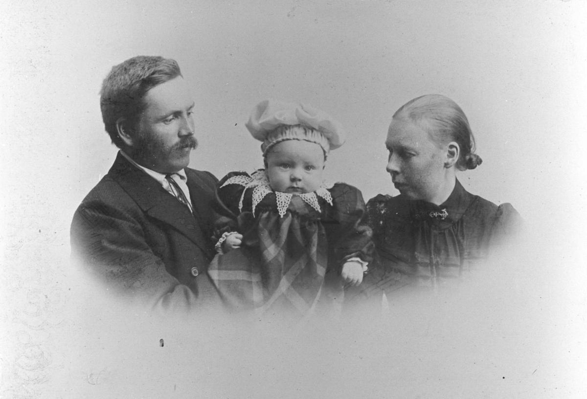Familieportrett av skreddermester Emil Halto med kona Hilda og sønnen Aage Halto. Faren står til venster med en lite barn i fanget og moren til høyre. Begge foreldrene ser på spedbarnet som er kledd i rutet kjole med hvit krage og hvit lue.Samme motiv som 03019-008.