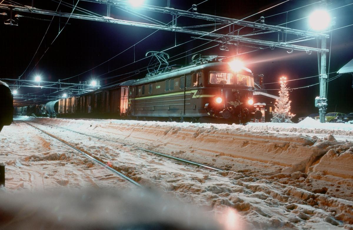 Julekort stemning i Eina stasjon. NSB godstog 5164, Gjøvik - Alnabru, står klar til avgang med elektrisk lokomotiv El 11 2090.
