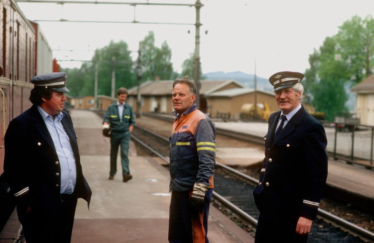 Personalet i godstogene 5174 (Eina - Roa) og 5166 (Roa - Grefsen) slår av en prat på Roa stasjon. Fra venstre lokomotivfører Edvind Jokerud, overkonduktør (togfører i tog 5174/5175) Harris Finnerud og lokomotivfører Martin Bråten. Alle stasjonert på Hønefoss (Oslo distrikt, det var også stasjonert kjørende personale fra Drammen og Bergen distrikter på Hønefoss). I bakgrunnen ser vi Knut Vestby, dentgang utvendig stasjonsbetjent på Roa. Konduktørvognen som sees til venstre er i tog 5174/5175. Konduktørpersonalet på Hønefoss stasjonert i Oslo Distrikt kjørte i hovedsak kun godstog.