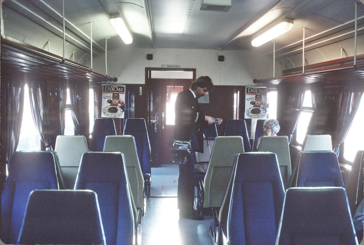 Interiør i dieselmotorvogn BM 86K 15 på Numedalsbanen. Toget var enmannsbetjent og lokomotivføreren kontrollerer billetter før avgang. Det var tre reisende fra Kongsberg denne dagen.