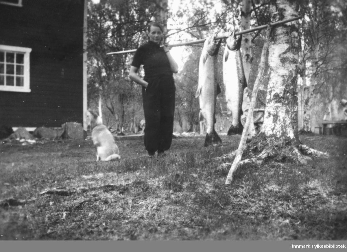 Magna Wisløff viser fram to store laks som henger fra en bærestokk. Til venstre for henne sitter en hund. I bakgrunnen ser vi et fjøs, gårdstun og trær. Ca.1930-40.