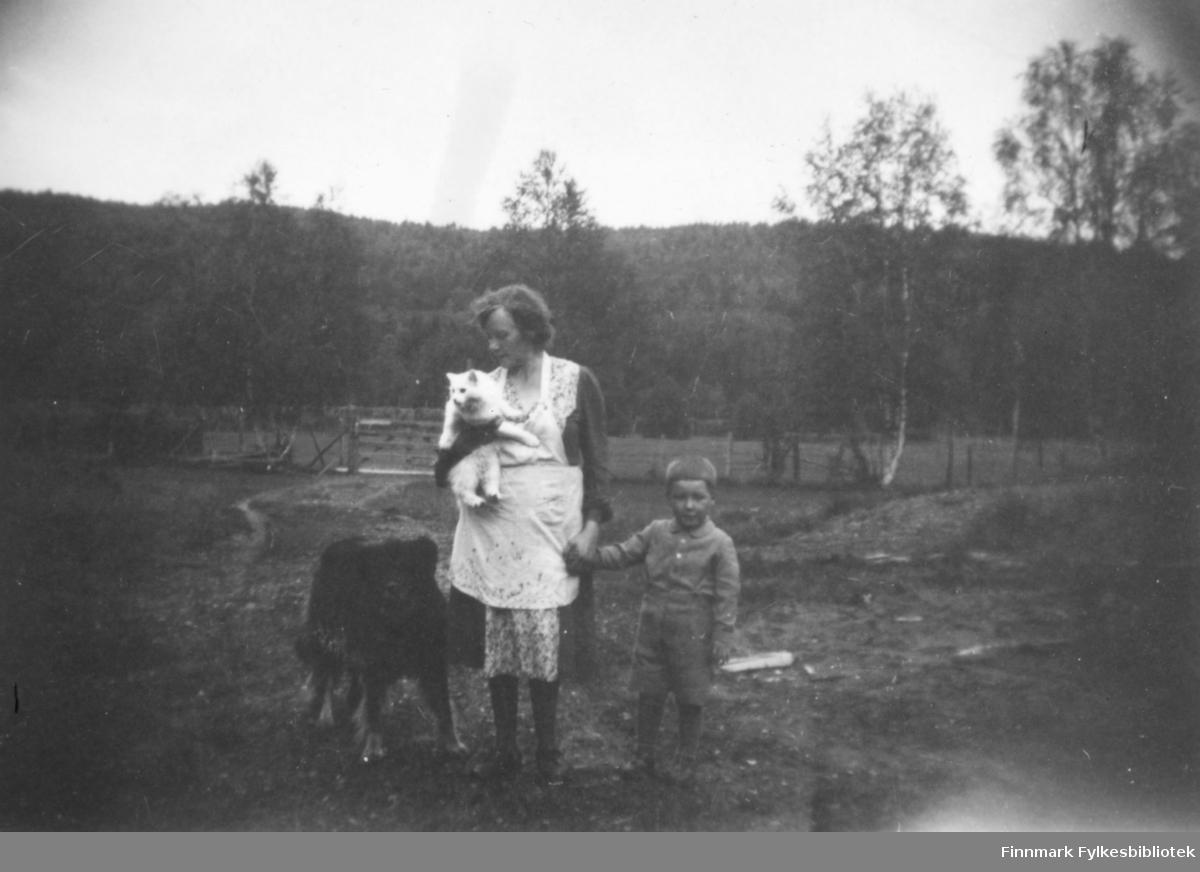 Magna Wisløff leier sin sønn Ole Arve Wisløff i hånden. Hun holder familiens katt og til venstre for henne står Kristian Wisløffs hund. Bak dem ser vi et gjerde og et jorde. I bakgrunnen tett skog. Ca.1945-50.