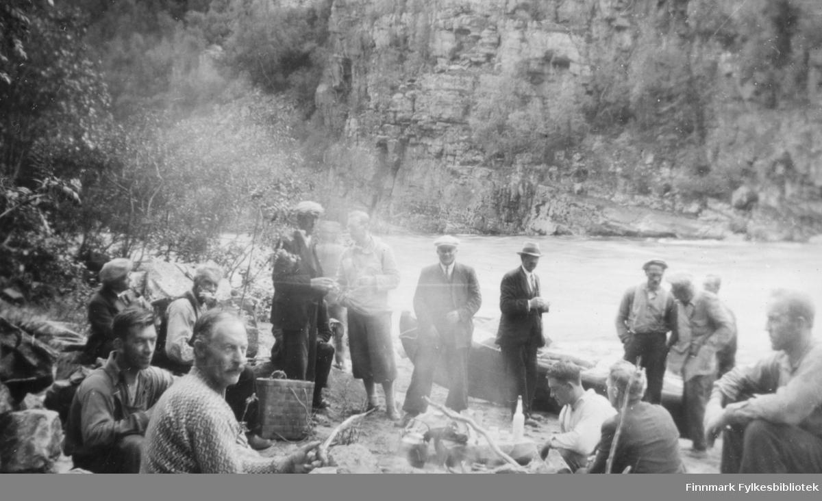 Elvebåtstakere har matpause ved Altaelva. Kristian Wisløff lengst til venstre. Vi ser kaffekoking på bålet, en trekurv som mat og drikke har blitt brakt i. En elvebåt ligger på stranden og i bakgrunnen ser vi Altaevla og dalsiden på andre siden. Mennene på bildet er både elvebåtstakere og menn i dress og slips. Ca.1940 -50.