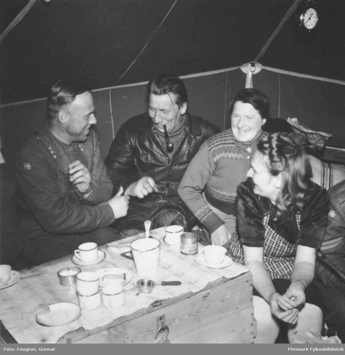 Sammenkomst i et militærtelt. En militær mann i uniform, en sivil mann i skinnjakke og med pipe og to sivile kvinner. De sitter rundt et bord laget av en trekasse. Det er dekket med duk og kaffekopper.