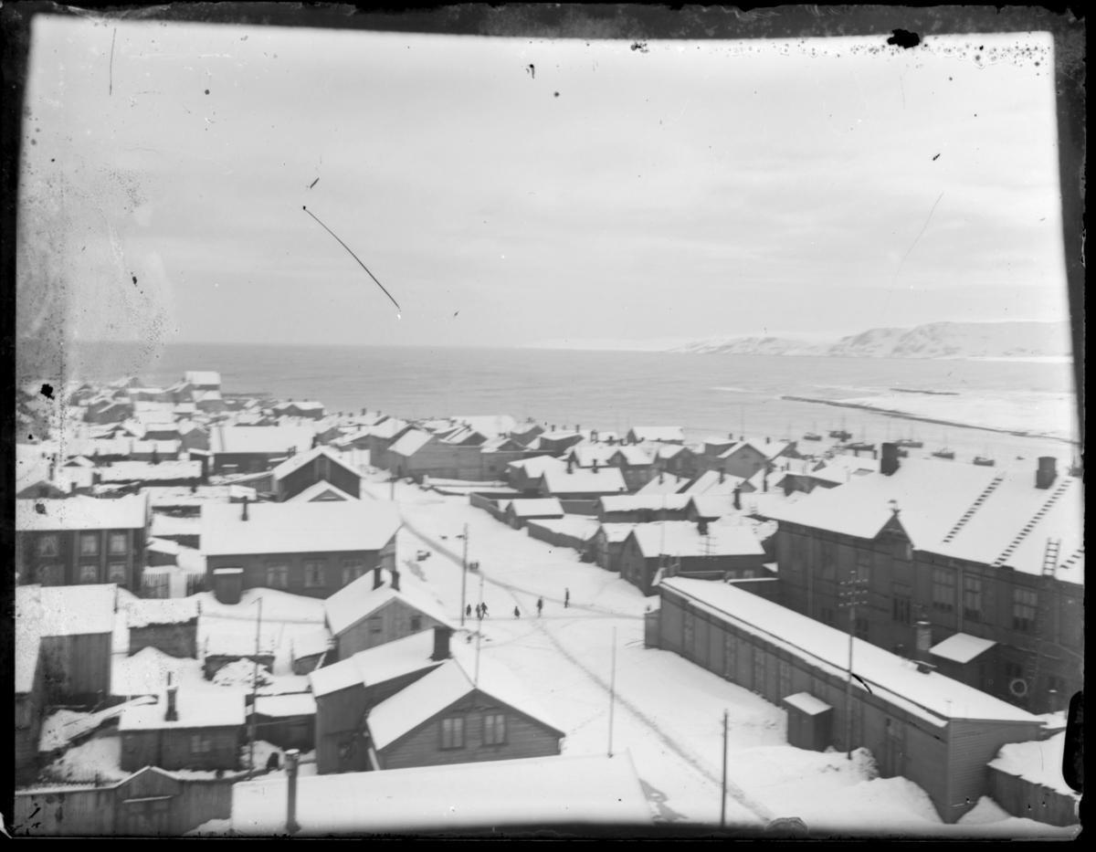 Bebyggelsen i Vardø antakelig fotografert fra kirketårnet. Bildet er tatt nedover Søndre Langgate, mot Søndre våg. Den store bygninga til høyre i bildet er rådhuset og samlaget, som var samlokalisert. Det ligger mye snø i gatene