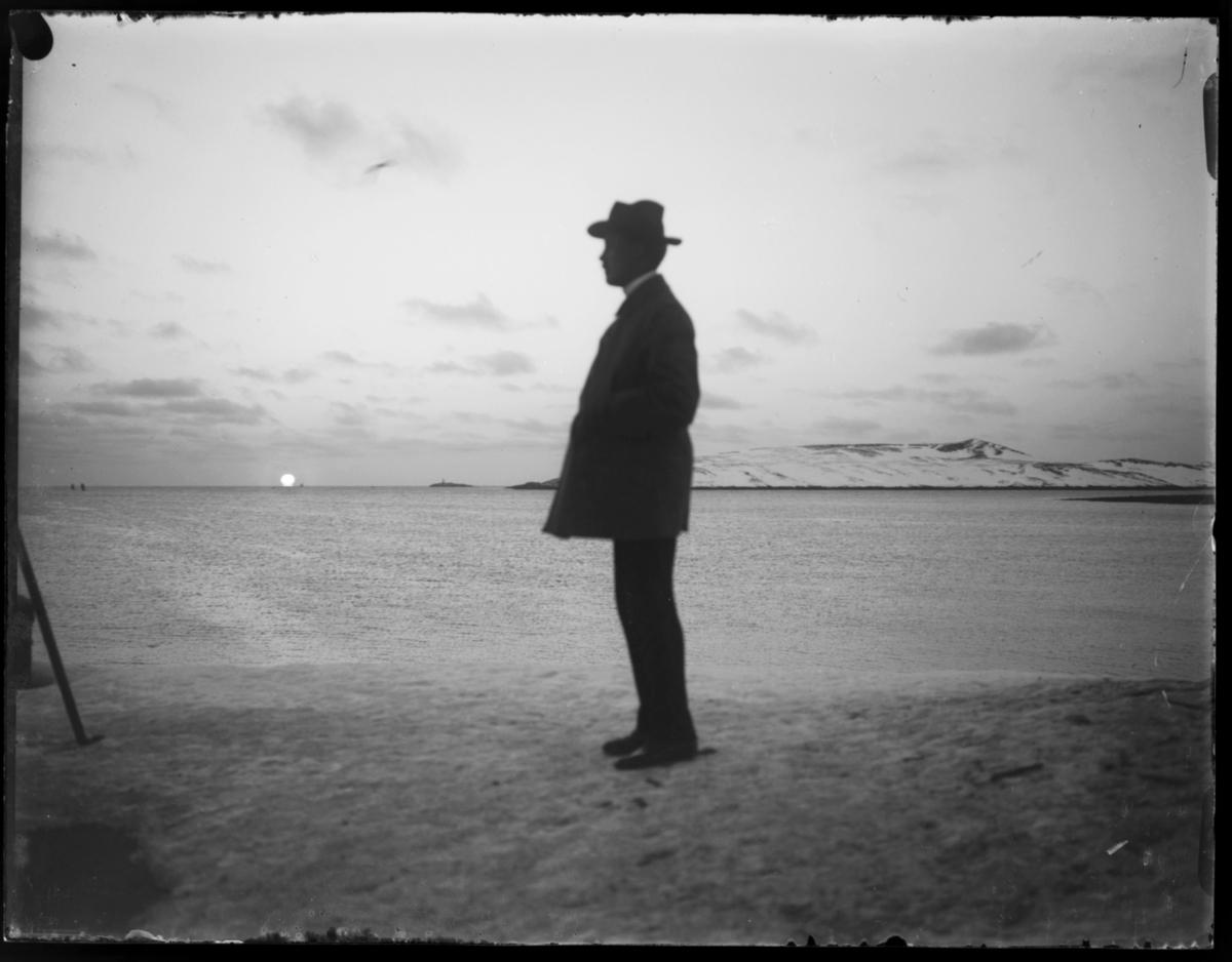 Mann fotografert i silhuett mot lav sol, han står antakelig på kaia i Vardø