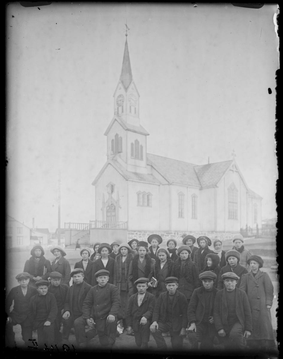 Konfirmanter i Vardø 1914, fotografert med Vardø kirke i bakgrunnen. Guttene sitter på kne foran, jentene står bak. Samme gruppe som FB 92144-002 til 007