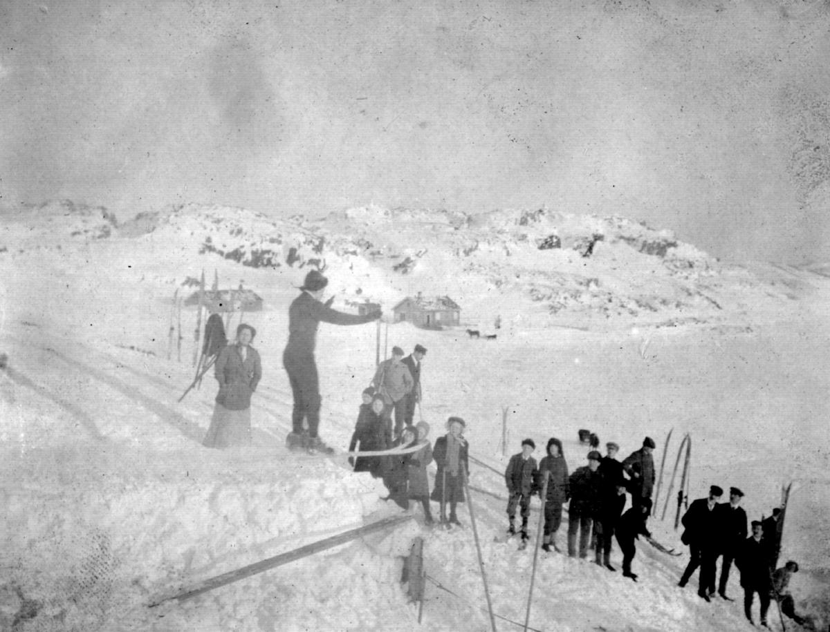 Flere mennesker som står og ser på en som står på kanten av en hoppbakke.