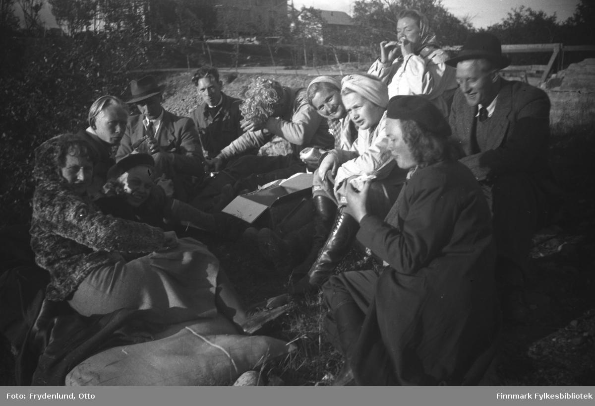 Folk fra Vadsø har tatt turen til Skipagurra i anledning Kong Haakon VIIs besøk 12. juli 1946. De fleste på bildet var ansatt ved Brente steders regulering. Her tar de en matpause
