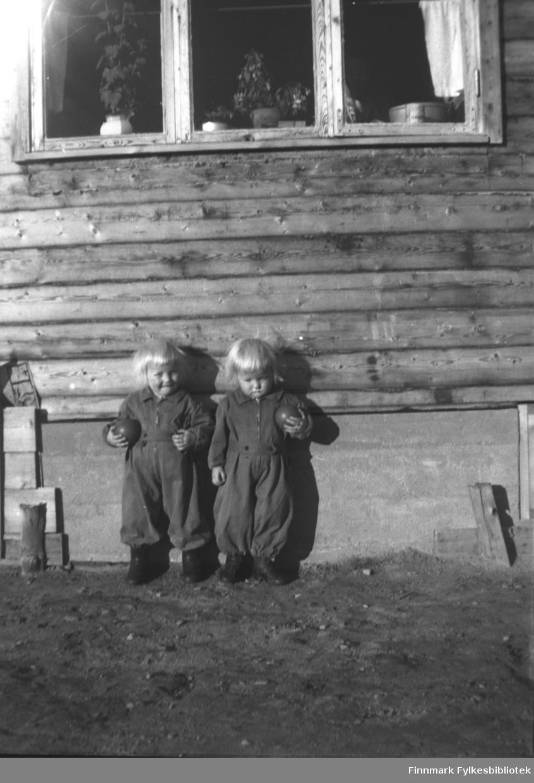 Tvillingene Unni og Lilli, barn av Arvid Mikkola. Bildet er antakelig tatt der barna bodde, i nærheten av A.K. Mikkolas butikk. De har like kjeledresser og holder hver sin identiske gummiball. Barna kan være 2-3 år gamle