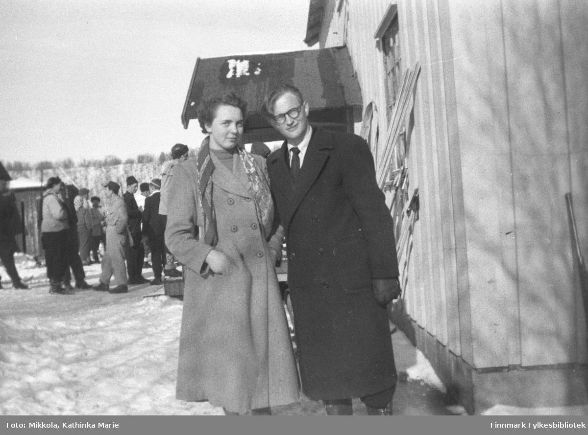 Utenfor A.K. Mikkolas butikk i Neiden, ganske mange mennesker er samlet. Foran fra venstre: Olaug Ingilæ som var hushjelp på internatet i Neiden og Erling Arvola.